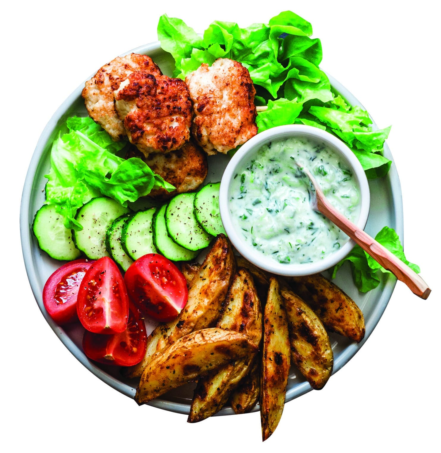 Fish skewers, baked potatoes, vegetables and yogurt greens sauce on dark background, top view
